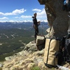 Ledge belay for Chinook, with gear bags at the base of Thorodin's Hammer, and the Continental Divide backdrop.