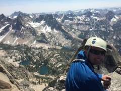 Bryce Parker on the summit of Warbonnet, Sawtooth Wilderness Idaho with the remote Goat Creek drainage. Breathtaking summit.