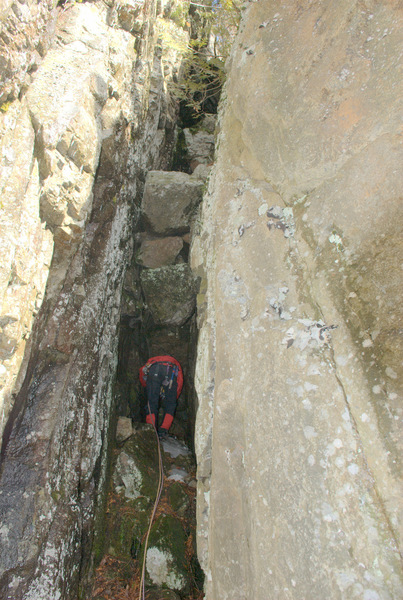 Starting up the overhanging chockstones on P1 of The Maw.