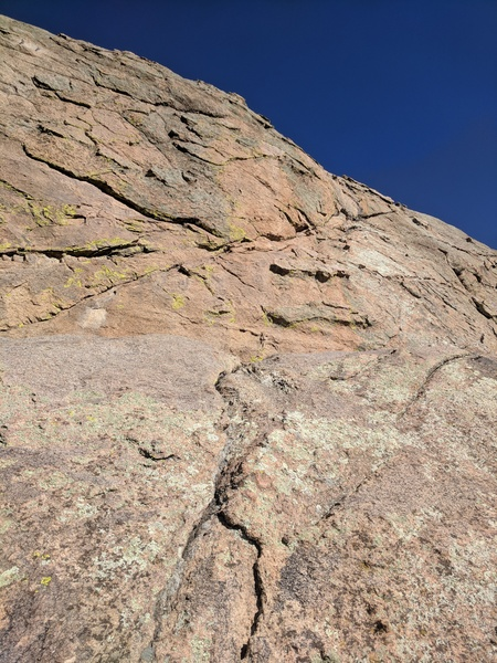 From the top of Chicken Shit, follow the right trending crack up the wall.  Top out on easy slab and walk all the way up to find a good crack system to build an anchor.