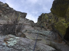 Jordan Nicholas starting into the dirt pitch (P4). Ben Correll visible at the belay station above.