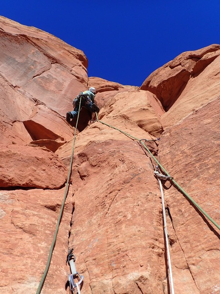 Starting up from the optional belay.  Notice the famed dirt clod on the bottom left.  Dance around it to the left crack and then move right about where the climber is in this photo,  If you stay right from the optional belay into the thin seam it climbs at about 5.11