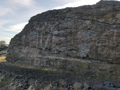 The left side of the stone wall boulder. V0 warmup up the middle. LR and RL traverse near the top.