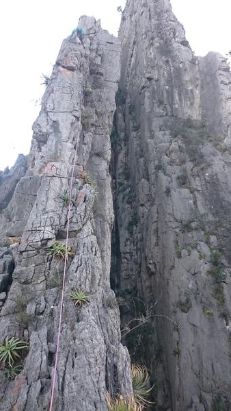 Partner climbing the crux pitch (P4) on Razorblade Ridge