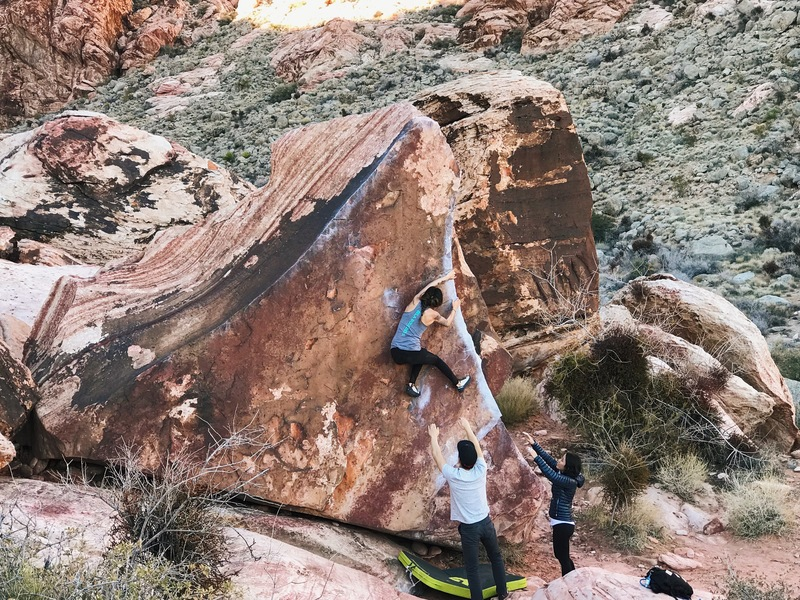Sarah on Pork Chop with the v4 start (undercling underneath the arete)