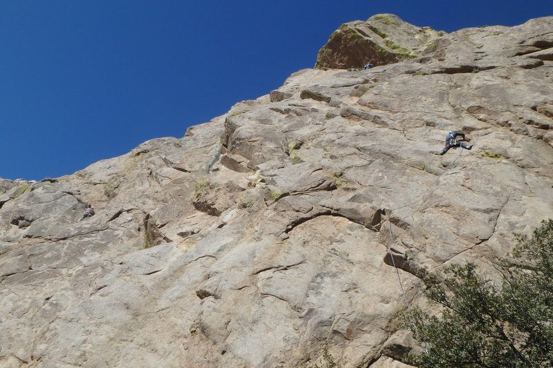 Forrest Wilcox (left) making the move up to the lone piton, prior to rapping down off of it due to the next no-pro section. A bolt or two are needed on this route. (also note climbers on Lowenbrau Light at left, and on Black Velvet toward the top)