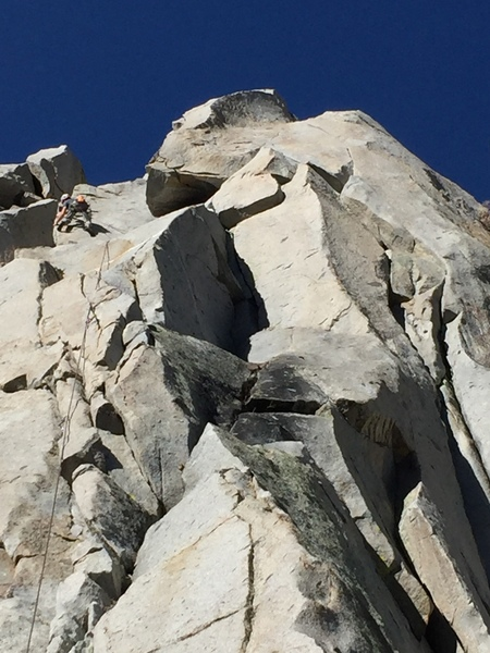 Climber on the top arete of Cotton Headed Ninny Muggins