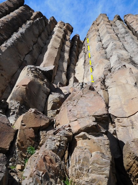 This picture shows the alcove that is on the right and up the crumbly slope from Under Duress. The yellow line is Climbing on Rainbows.