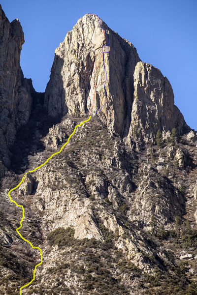 The east face of North Rabbit Ear as seen from Aguirre Springs Campground.<br> YELLOW: East face approach gully, accessed from Baylor Peak trail.<br> RED: Sleight of Hand 5.11- ***<br> GREEN: established variations<br> BLUE: Hand Jive 5.8+ ***