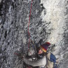 Rainsford Rouner cleaning the crux aid pitch on a late winter ascent of the Warlock in 1975