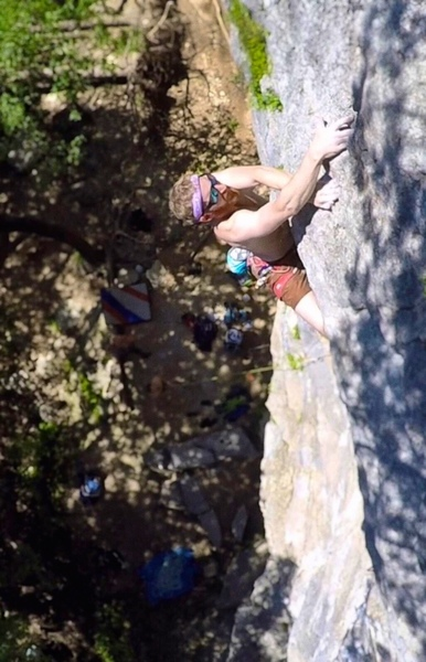 Reaching the good holds just over the crux buldge