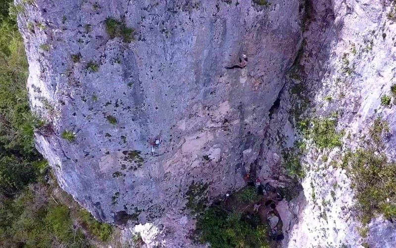 """Drone view of the shady wall with climbers on (L) Blanca Nieves """"Snow White"""" and (R) Que Siga La Rumba """"Follow the Rumba (music)""""."""