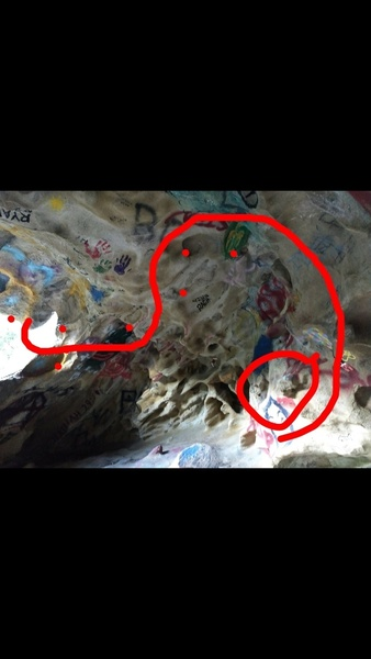 Sit start on jug in graffiti cave, move up to big painted jug above the starting one, then move to the left towards undercling tufa jugs on ceiling, swing over to rail and undercling towards the opening of cave and finish there.(v4)