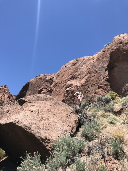 The Little Sheep Wall as seen from the river bed.  fiance for scale.  The area where you'll set up for belaying is just behind the boulder to the left of my fiance.