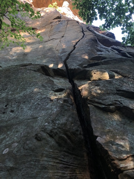 Wide crack tapers to tight hands before the small ledge, step left & pull onto slab w/ finger crack (right side of the small arete in top of pic).