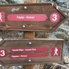 Signs visible from access road, showing the hiking trail that leads to the Kamari climbing area.  Take the sign pointing right, which leads downhill to the climbing area, about a ten minute walk.  You can park at these signs.