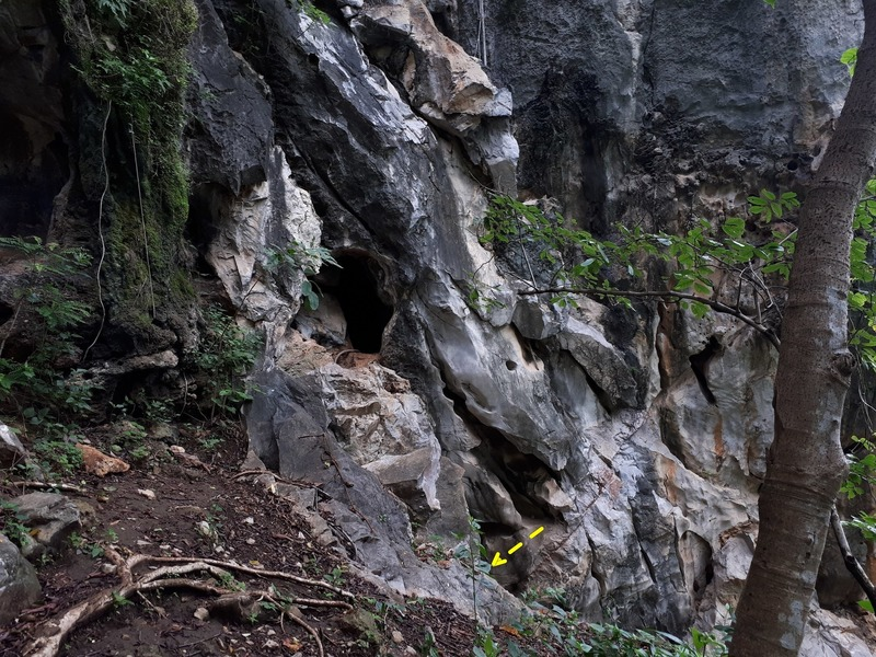 View of the entrance, from the trail. (The larger cave opening above and to the left leads out to Crazy Horse Buttress.)