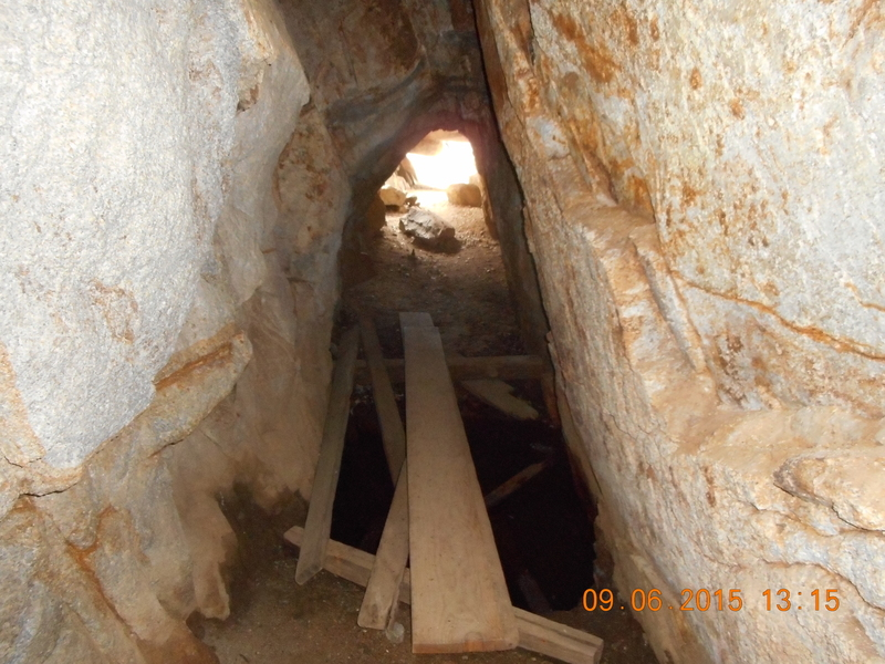 Cave entrance has a wooden plank to step over the underground spring.