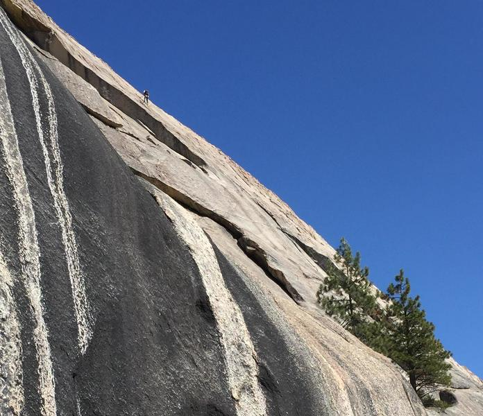 Starting ledge is right of 2 pines (lower right). P2 dihedrail is shadowed upper left. Dihedral exit is where dark and light rock meet near upper left corner. Climber is on Crossing the Milly Way.