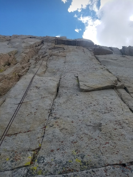 Looking up at pitch 3, route follows bolt line on face to right of rope.