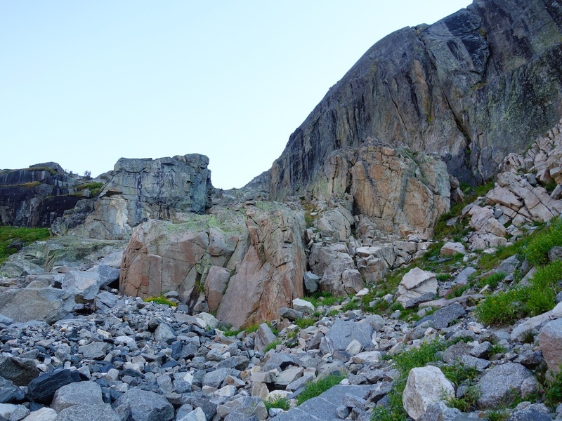 """Skirt left below rock walls until you come to the giant square-shaped slot (the """"Garage Door""""). Then cut right up the grassy/rocky slopes to the base of the route."""