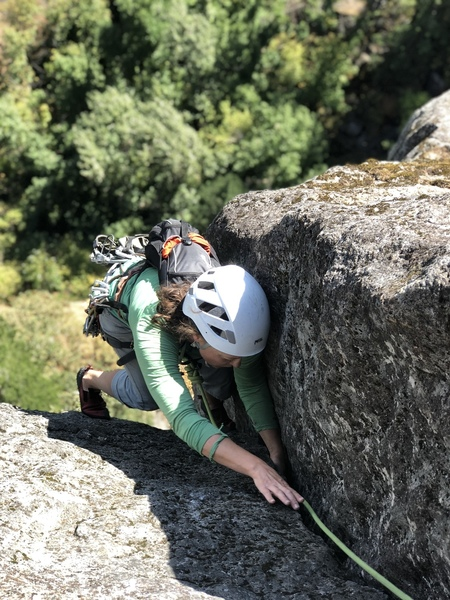 Looking down Dod's Jam; climber (Amy S.) is past the crux. Here the crack widens to #2 Camalot size and the angle eases for an easy 20' of jamming past a two bolt rap anchor to Big Ledge.
