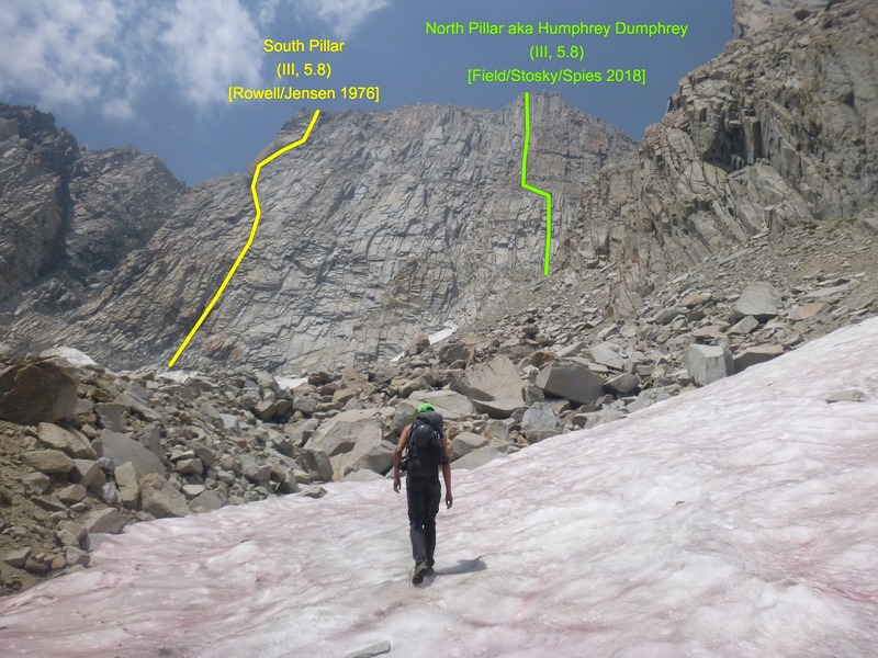 Steve approaches the massive east face of Humphreys in mid-summer conditions. Yellow and green lines show the known routes on the wall.
