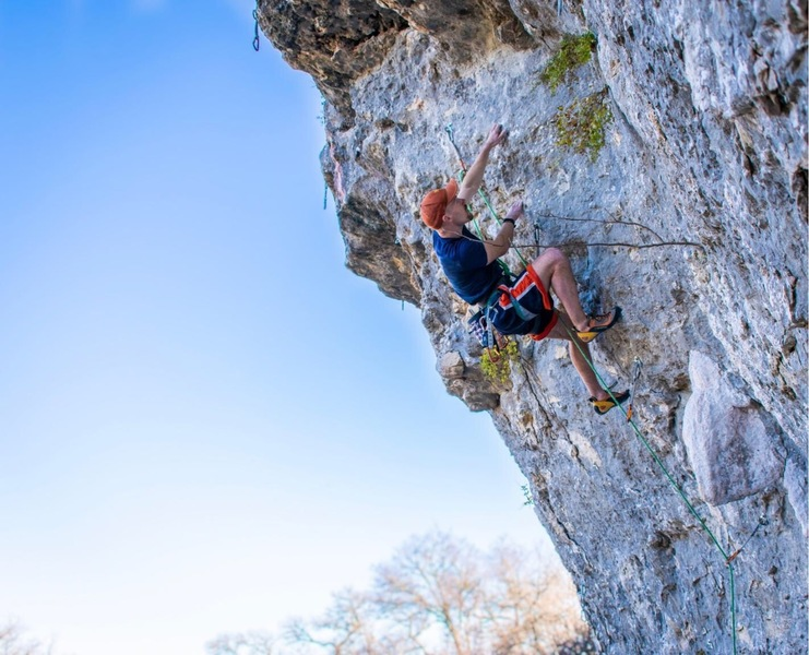 """Kelly making a cross through the upper crux of the route. The large white """"fang"""" feature that gives the route it's name can be seen just above the first QuickDraw pictures here"""