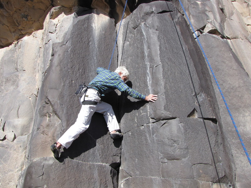 """Moment of Inertia climbs the left of two similar dihedrals. The dihedral to the right of the climber is a wholly separate climb, """"Obsidian Corner"""". Chuck Calef is beginning the lower crux sequence which involves long reaches to sloping glass."""
