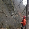 Chuck belaying, from below the route, while leaning back against the belay tree