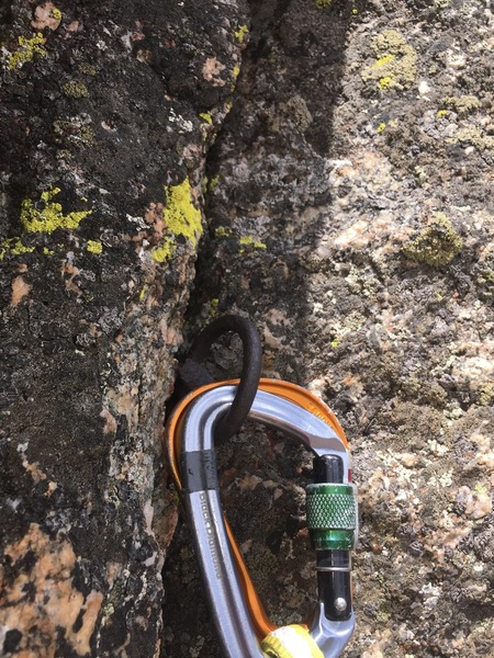 The fixed pin on the steep 4th Class downclimb to the notch. An orange carabiner was there (and still is) along with the pin. Held body weight when tested.