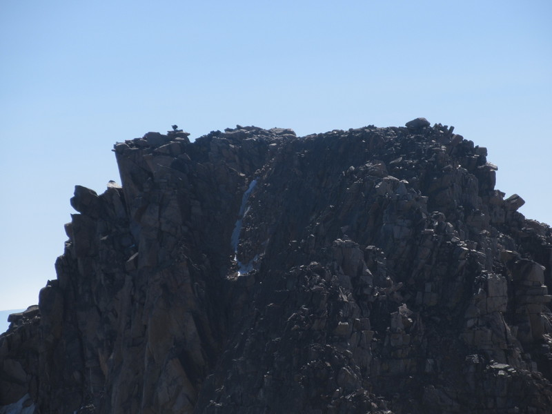 A climber signing the summit log of Granite Peak, seen from West Granite Peak. YOU have a ways left to go, my friend!