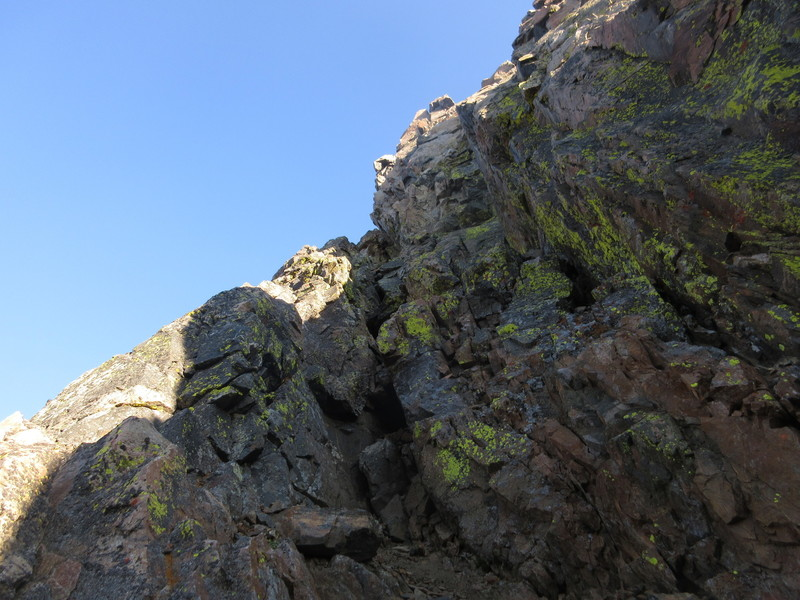 Ascending the loose and fractured chimney crux of the traverse.