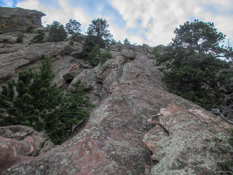 About 20 feet below the jump, which blends into the photo in the middle. The route continues straight up to the end of the rock then left and up on two more slabs to the hiking trail.