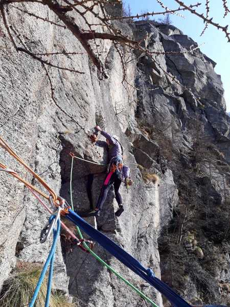 Evija trying to solve the boulder problem at the start of p3