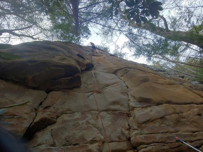 Brad on the first ascent. It starts up the crack to the left, under the roof.