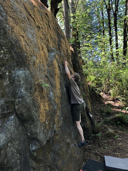 Isaac Lee reaches for the ledge on Gumby Slab