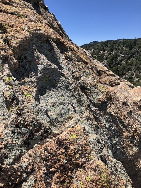 Possibly where the rap anchor used to be on the back side of the summit? The scramble down to the saddle is not too difficult without it.