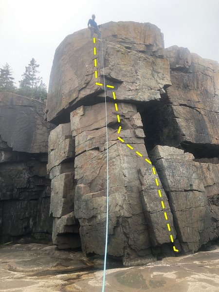 The route starts just left of the off-width ( on right side of photo). Move up the face to the obvious stances, then angle up and left to a stance on the arête. Move up to the overhang, pull yourself up, then finish up either face. That's how I did it.