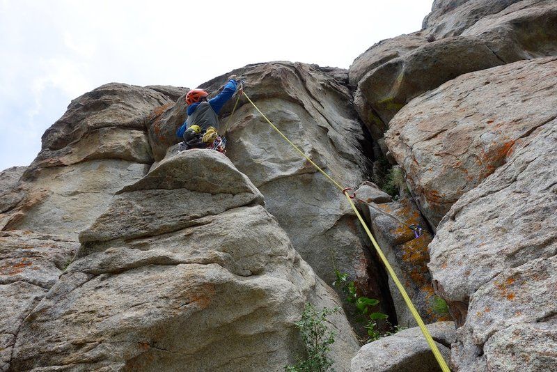 Clipping the bolt that protects the crux move.