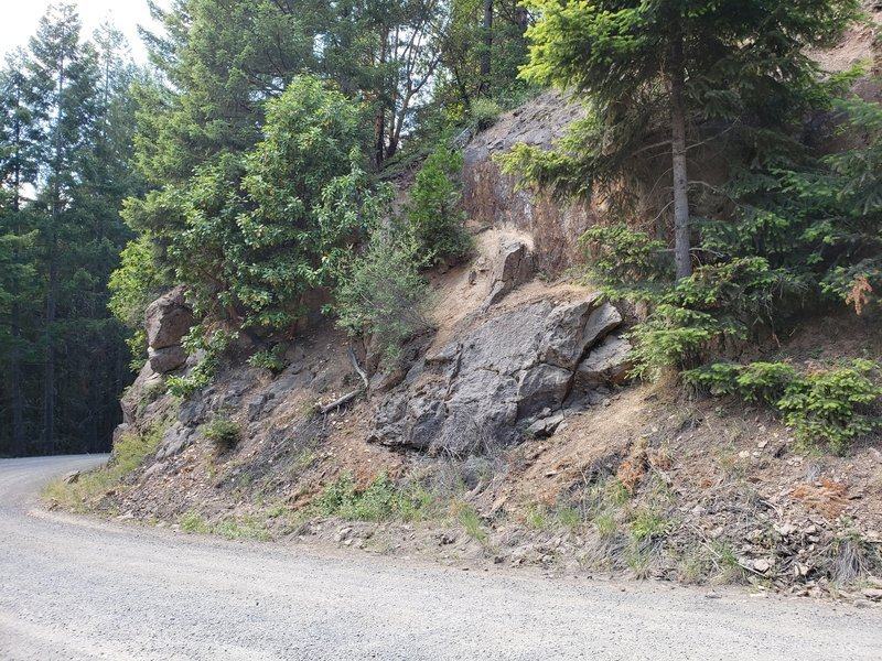 View of the base of the approach trail from the road. Scramble up the hillside and traverse across to the left using the handrails. T-Rex Rock and others will be to the right (east), Stegosaurus Rock will be uphill.