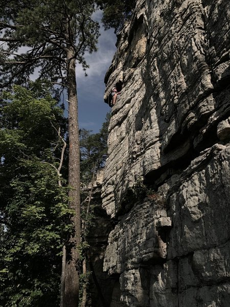 """Rounding the """"pole"""" (arete) below the roof, a fun move with good exposure."""