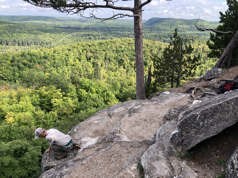 Top of Sawmill Creek Dome. Conner looking over edge. Top of Birch Flakes is right by the big tree in center of photo.