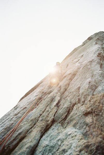 manny s. leading the second pitch of 'central pillar of frenzy' as the sun peaks over middle cathedral rock