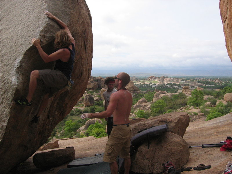 Travis Eiselstien working his way up Arete on the Cosmic Friction Boulder in Hampi, India.