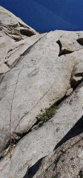 P3 seen from the base. Unfortunately the old aid line is no longer any good, as the tat to reach the right corner TT is old and shortened, and the bolt looked bad. There is a piton on the left of the ledge protecting the entry mantle into the crack.