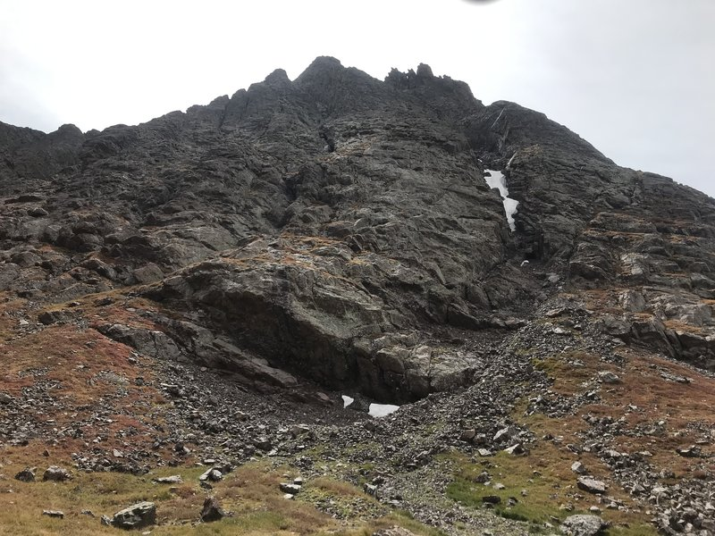 Gain the grassy ledges to the left of the large roof. The route continues above the roof and to the left of the gully with snow.