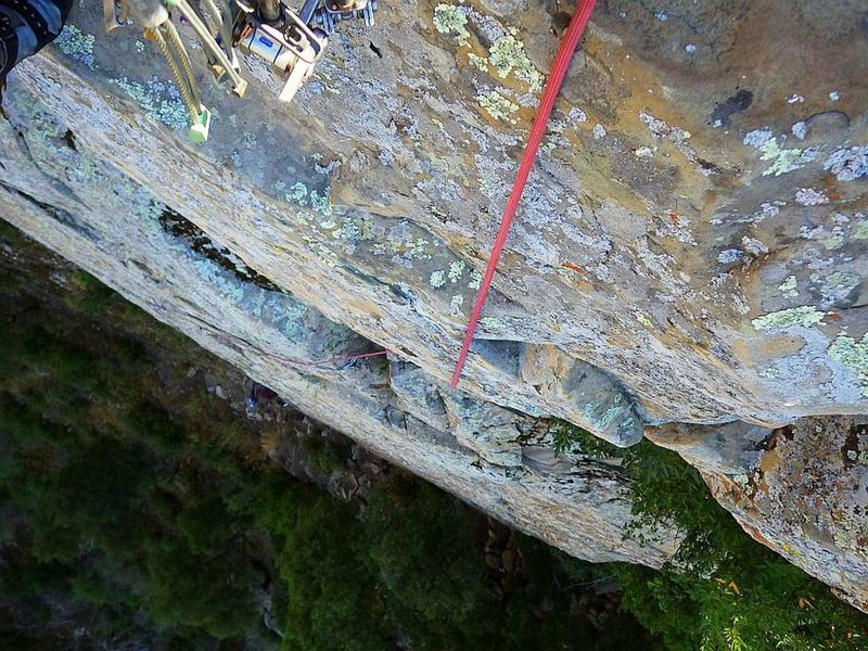 Leading up and over the big summit roof, veering left toward the anchor bolts, with Caiti way below.  15 Oct 2019.
