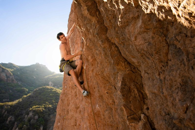Honnold on pink wall... using a rope...