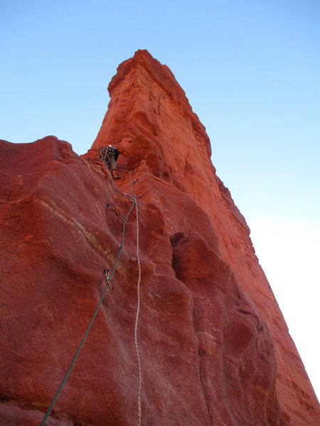 Dirk at the end of the bolt ladder on P3, about to begin the mixed 5.7 free and C2 aid climbing to reach the lower anchor.